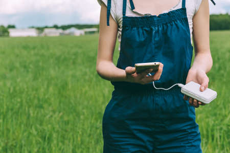 close-up of charging the phone from the pover bank in the hands of a farmer girl. against the background of agriculture 스톡 콘텐츠 - 155372203