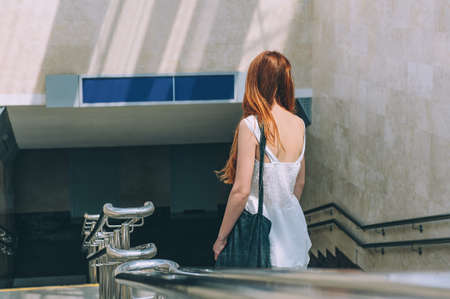 The red-haired girl walks down the stairs to the tunnel, from the train station to the airport