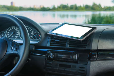 Tablet mockup, on the car dashboard. Against the background of a river, lake, a concept on the theme of tourism
