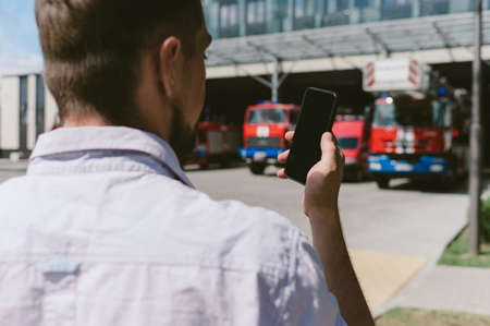 A man holds a mobile phone in his hand in front of his face. Against the background of fire trucks