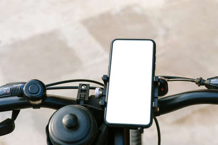 Close-up, mockup of a smartphone on the handlebars of a bicycle. Against the background of concrete and asphalt