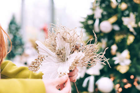 The girl holds decorative flowers in her hands. Against the background of the counter in the store. Concept on the theme of kindergartens for Christmas and New Year