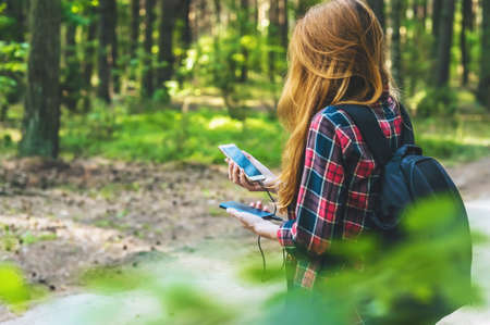 Power bank and smartphone in the hands of a girl with red hair in a shirt in a cage with a black backpack, on the background of a forest road Archivio Fotografico