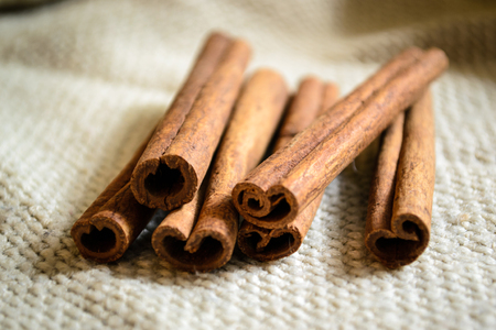 Spices cinnamon sticks on the cloth on a wooden table