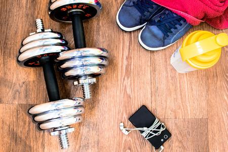sports equipment on the wooden floor with sneakers, telephone, headphones, dumbbells, towel.