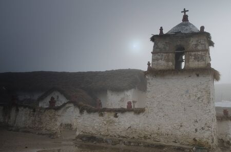 Church and bell tower of Parinacota in a fog. Lauca National Park. Arica y Parinacota Region. Chile.