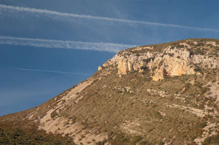 Airplane, contrails of another airplanes and cliff. Natural Park of the Mountains and Canyons of Guara. Huesca. Aragon. Spain.
