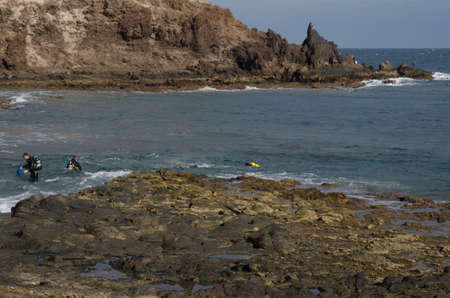 Divers coming out of the water. Green Cliff. Arinaga. Aguimes. Gran Canaria. Canary Islands. Spain.