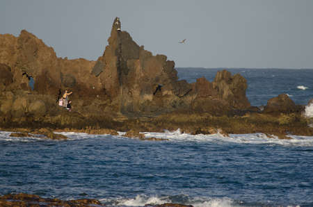 People throwing flowers into the sea. Risco Verde. Arinaga. Aguimes. Gran Canaria. Canary Islands. Spain.