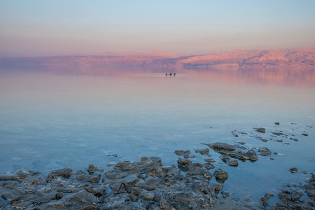 Lovers floating on the Dead Sea by sunset time. On the background, the Jordan mountains turn red by this time of the day. Imagens - 91043470