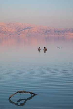 Kids swimming in the dead sea of Israel by sunset time. On the background, the Jordan mountains turn red by this time of the day. Imagens - 91043478