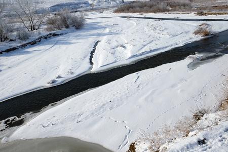 Sarykum barchan 근처에 동물 산책로가있는 겨울에는 얼음없는 산 강이 있습니다. 러시아 다게 스탄 스톡 콘텐츠