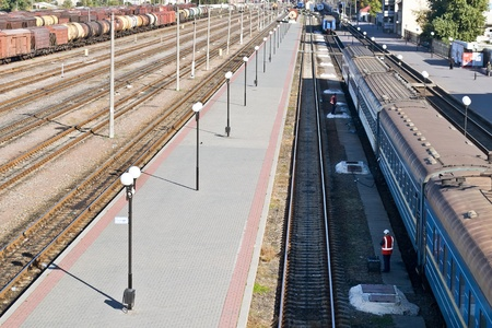a perspective view of station with set of parallel rail lines and platform with carriages photo