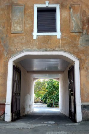 a view of an archway with partio behind in old provincial town street Фото со стока
