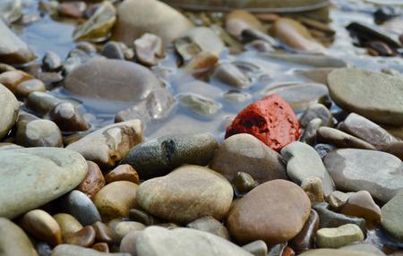 Eine rote Fluss Stein unter großen Menge der grauen Fluss Steine ??als Symbol der Einzigartigkeit oder Einsamkeit
