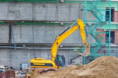 contruction:  excavator yellow on the background of the building under construction
