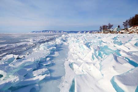 Beautiful landscape of the frozen Lake Baikal on a sunny winter day. Fields of ice hummocks near the shore in the village of Listvyanka. Standard-Bild