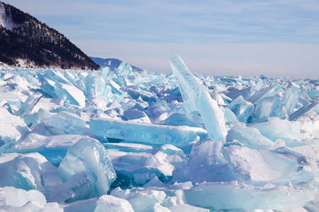 Beautiful landscape of the frozen Lake Baikal on a sunny winter day. Piles of blue ice fragments covered in snow.