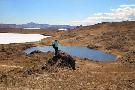 Lake Baikal, Olkhon Island in the spring. A girl looks at Lake Nuku-Noor or Lake Heart. Traveling alone.