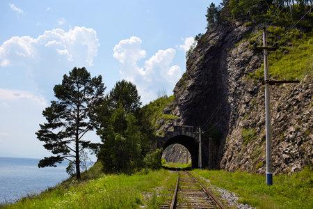 Baikal lake in summer. Old stone arch tunnel in mountain the rock on the Circum-Baikal railway.