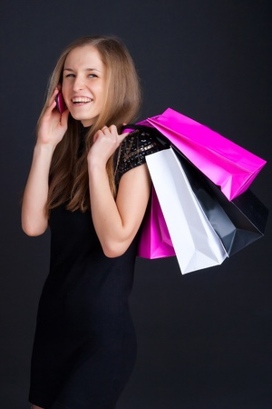 Girl with shopping on the phone and smiling photo