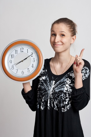 beautiful girl with a big clock in his hand raises his index finger up photo
