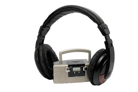 Little radio and big headphones on white background