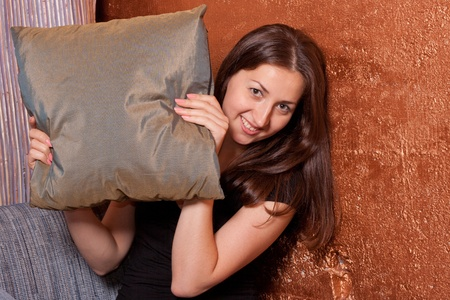 coquettish: the girl looks out of pillows and coquettish smiles