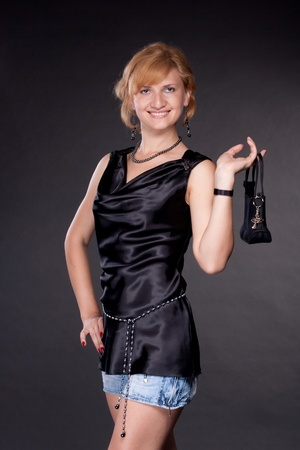 The girl, dressed in black with a bag on a dark background photo