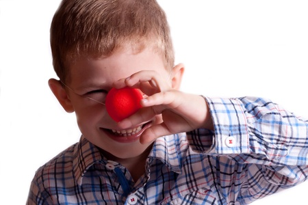 A little boy with a clown nose on a white background photo