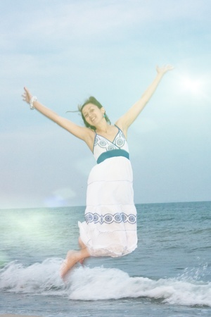 Happy girl jumps up on the beach   photo