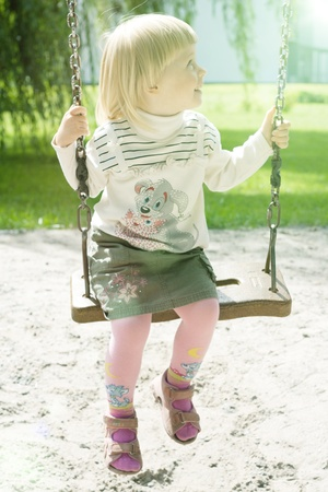 Year-old girl riding in the park on a swing Photo Stock Photo
