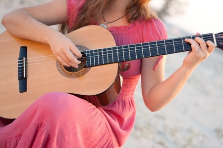 A girl in a dress playing a guitar shot on the nature photo