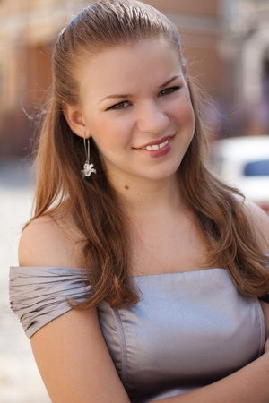 Portrait of a beautiful girl in a dress the color of steel shot in the street Stock Photo