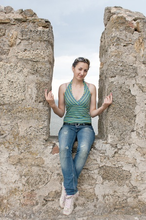 A girl sits in a niche of a stone wall photo