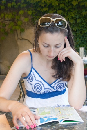 A girl in a summer cafe reading the menu outdoors shooting photo