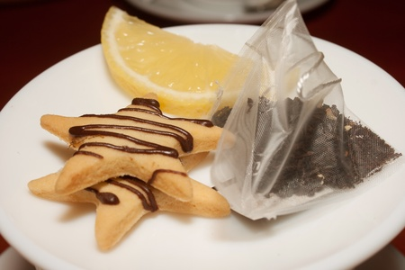 Tea bags, lemons, cookies, cup and spoon in a cafe shooting photo