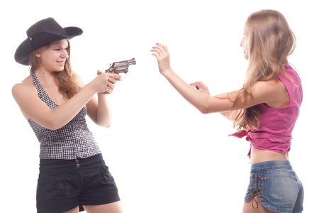 Portrait of two young girls with a gun shooting studio photo