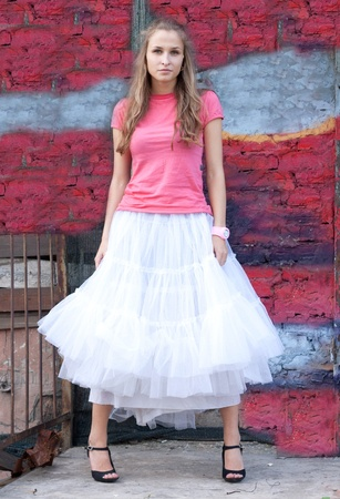 girl in white skirt and pink T-shirt in the city photo