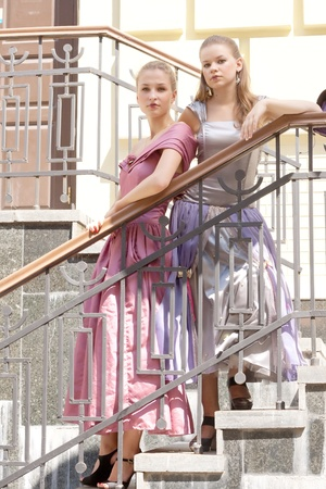 Two girls in beautiful dresses on the stairs shooting outdoors photo