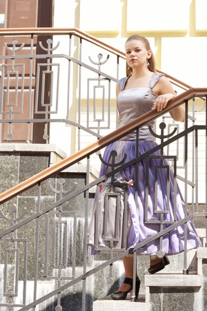 Beautiful girl in beautiful dresses on the stairs shooting outdoors photo