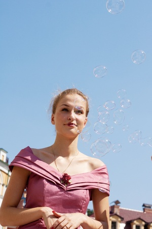 Beautiful girl with soap bubbles against a background of sky homes and shooting outdoors photo