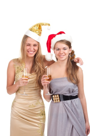 Two girls celebrate Christmas with gifts and glasses in their hands studio shooting photo