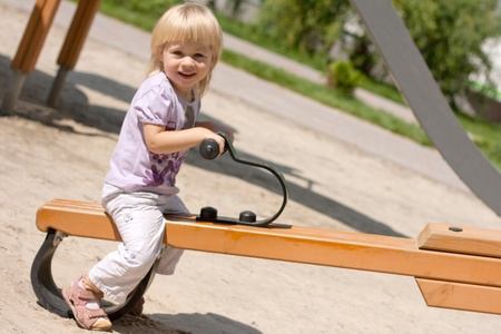 Little girl on a swing at the playground photo