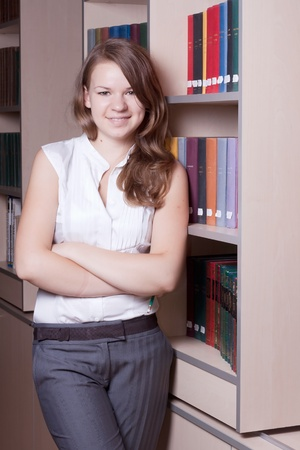 Beautiful girl in the library among the books photo