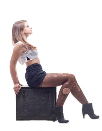 Beautiful girl sitting on a box of studio photography