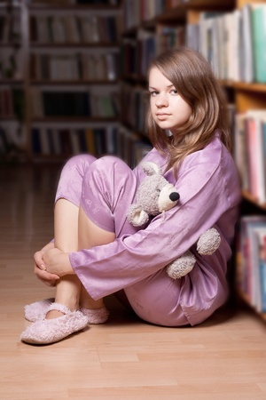 The girl in pink pajamas in the library among the books photo