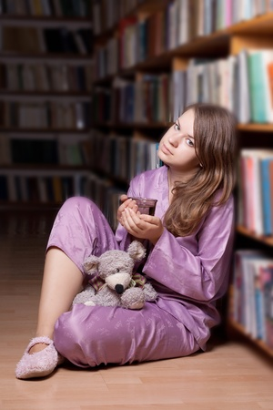 The girl in pink pajamas in the library among the books Stock Photo - 11134311
