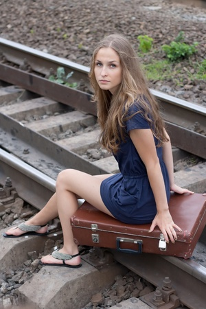 Woman sitting on rails outdoors shooting photo