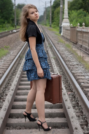 Girl with a suitcase standing on the rails shooting outdoors photo